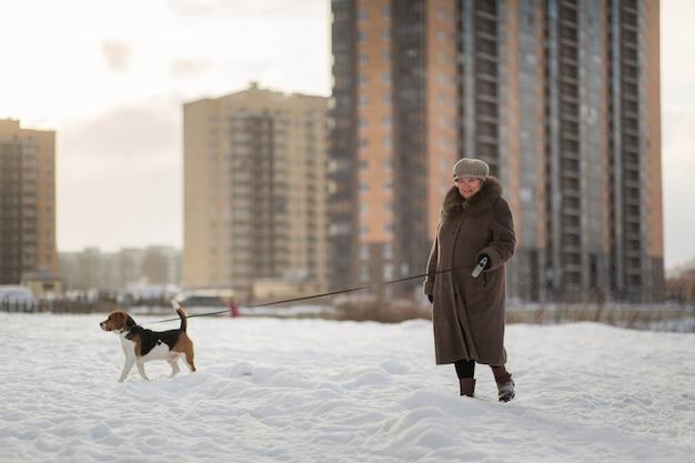 Vrolijke vrouw die met een hond op een weide in de winter loopt