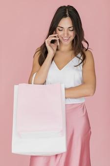 Vrolijke vrouw die met het winkelen zak neer kijkt