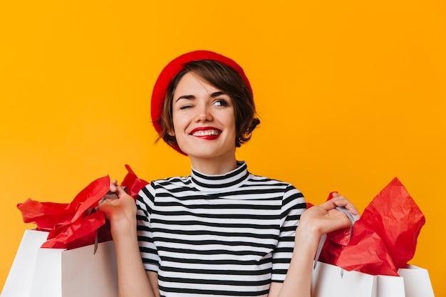 Vrolijke vrouw die met winkelzakken met glimlach opzoeken