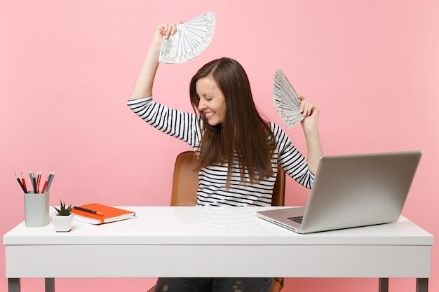 Vrolijke vrouw die naar beneden kijkt, gespreid zwaaiende handen met bundels veel dollars contant geld werkt op kantoor aan een wit bureau met pc-laptop