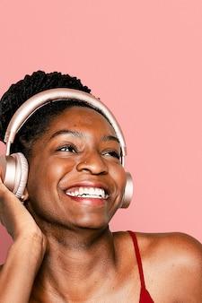 Vrolijke vrouw die naar muziek luistert via een digitaal hoofdtelefoonapparaat