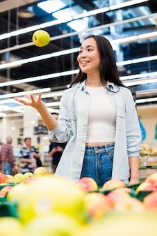 Vrolijke vrouw die omhoog appel in kruidenierswinkelopslag werpt
