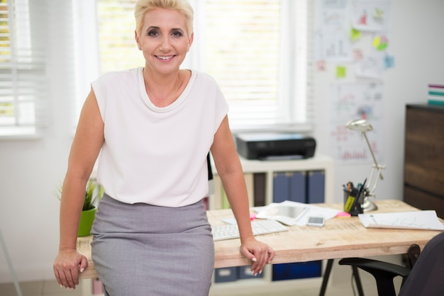 Vrolijke vrouw die op het bureau leunt
