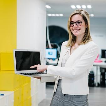 Vrolijke vrouw die op laptop vertoning richt