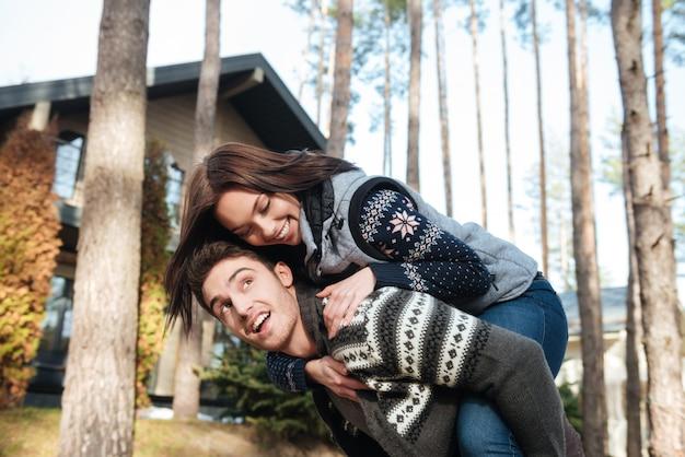 Vrolijke vrouw die op rug van haar glimlachende jonge man berijden die weg bos bekijken