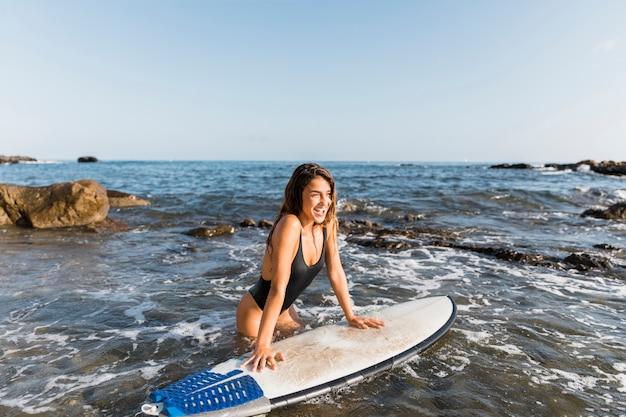 Vrolijke vrouw die op surfplank dichtbij kust leunt