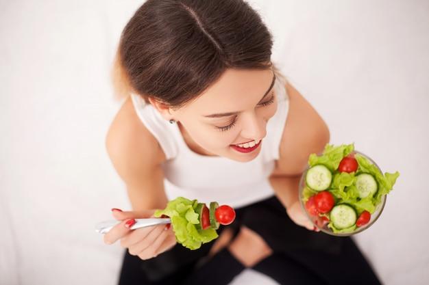 Vrolijke vrouw die plantaardige salade eet