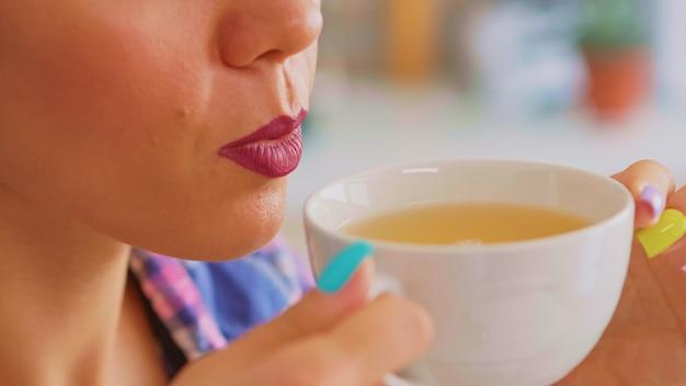 Vrolijke vrouw die 's ochtends hete groene thee drinkt. close up van mooie dame zittend in de keuken in de ochtend tijdens het ontbijt ontspannen met lekkere natuurlijke kruidenthee uit witte theekopje.