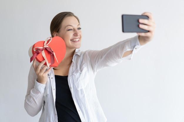 Vrolijke vrouw die selfie foto met hart gevormde giftdoos neemt