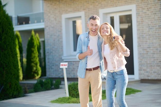 Vrolijke vrouw die sleutel en man toont dichtbij huis