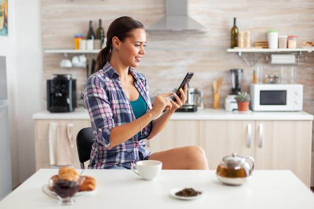 Vrolijke vrouw die smartphone in keuken gebruikt tijdens ontbijt en armoatic groene thee