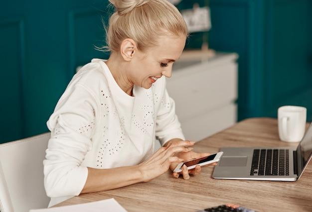 Vrolijke vrouw die sms leest op kantoor aan huis
