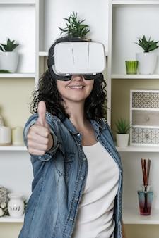 Vrolijke vrouw die virtuele werkelijkheid goedkeurt