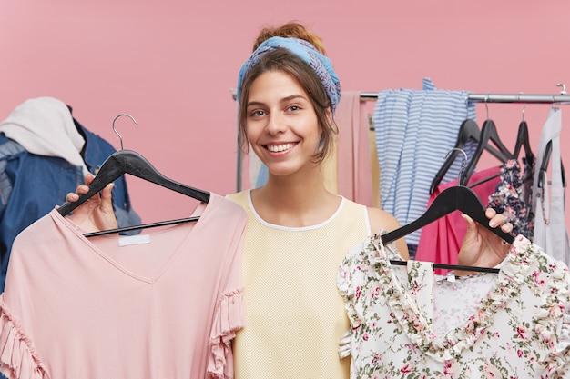 Vrolijke vrouw draagt sjaal op hoofd en shirt, lacht aangenaam terwijl ze hangers met twee jurken vasthoudt en is blij om ze allebei in de kledingwinkel te kopen. vrouwelijke verkoper die kleding adviseren te kopen