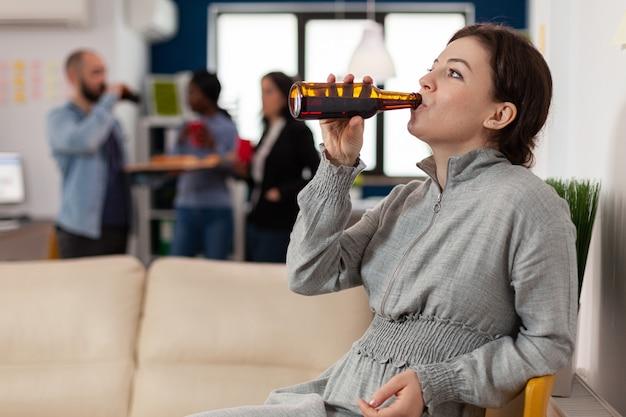 Vrolijke vrouw drinken uit flesje bier na het werk op kantoor met collega's. collega's ontmoeten elkaar op feest met eten en drinken om samen pauze te vieren. leuke activiteiten genieten