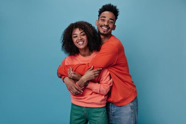 Vrolijke vrouw en man in oranje sweatshirts knuffelen op blauwe muur