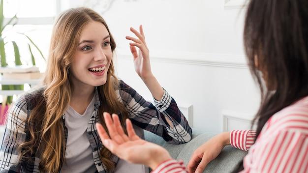 Vrolijke vrouw gebaren praten met vriend