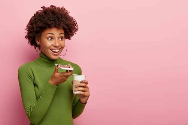 Vrolijke vrouw gebruikt spraakopdrachtrecorder, houdt smartphoneapparaat in de buurt van mond, geniet van aromatische drank drinken, draagt groene coltrui