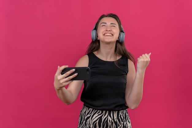 Vrolijke vrouw, gekleed in een zwart hemd, luistert muziek uit een koptelefoon op een roze muur
