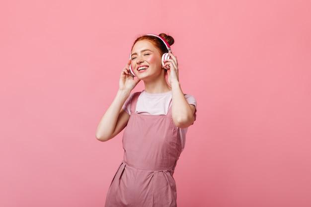 Vrolijke vrouw gekleed in lichte overall dansen en luisteren naar muziek op koptelefoon op roze achtergrond.