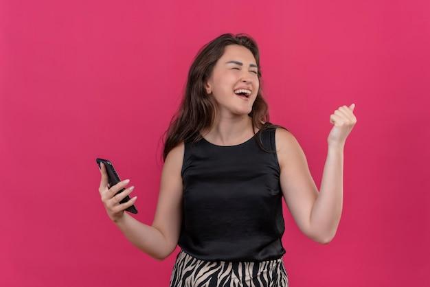 Vrolijke vrouw, gekleed in zwart hemd, luistert muziek van de telefoon op de roze muur