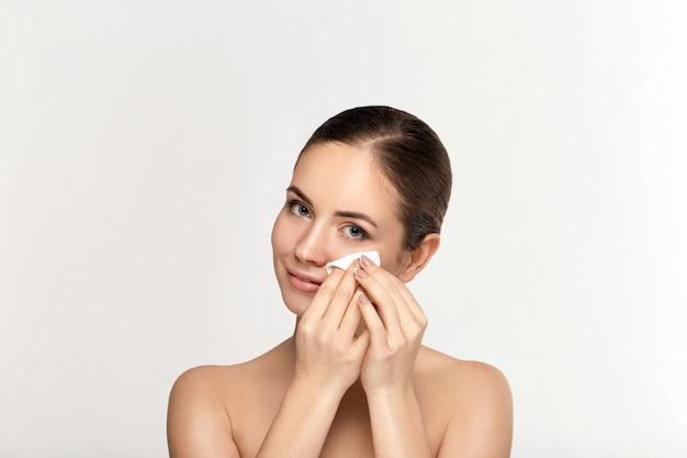 Vrolijke vrouw gezicht make-up verwijderen met een wattenschijfje op witte muur