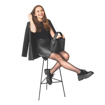 Vrolijke vrouw glimlachend en zittend op een stoel. jonge vrouw in zwarte jurk met zwarte leren tas, sexy benen met laarzen, zakenvrouw concept foto geïsoleerd op een witte achtergrond