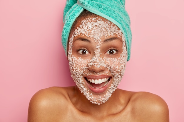Vrolijke vrouw glimlacht positief heeft wenkbrauwen ogen, verzorgt de lichaamshuid goed, draagt zeezout scrub om de teint te reinigen