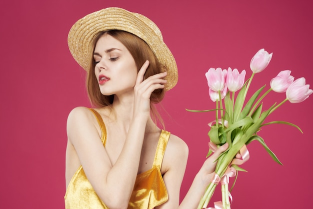 Vrolijke vrouw gouden jurk boeket bloemen vakantie roze achtergrond