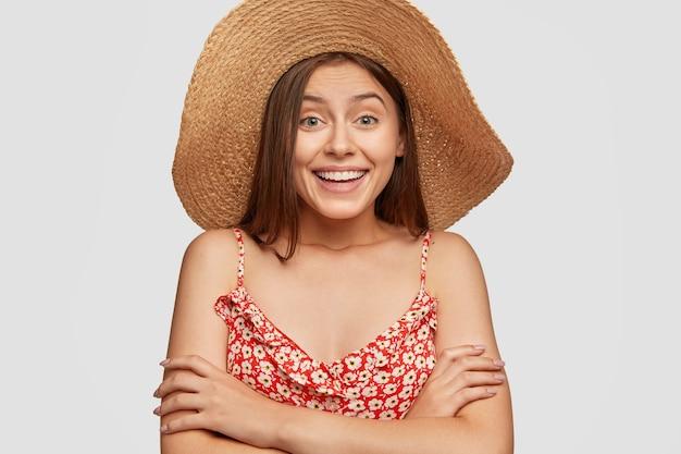 Vrolijke vrouw heeft een aangename glimlach, knuffelt zichzelf, is onder de indruk van goed nieuws, verheugt zich op vakantie, gekleed in modieuze outfit