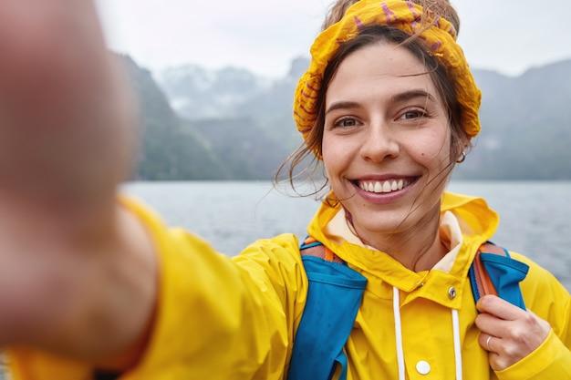Vrolijke vrouw heeft expeditietour, maakt selfie-portret, strekt zich uit in de camera, glimlacht breed