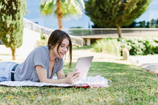Vrolijke vrouw het doorbladeren tablet in park