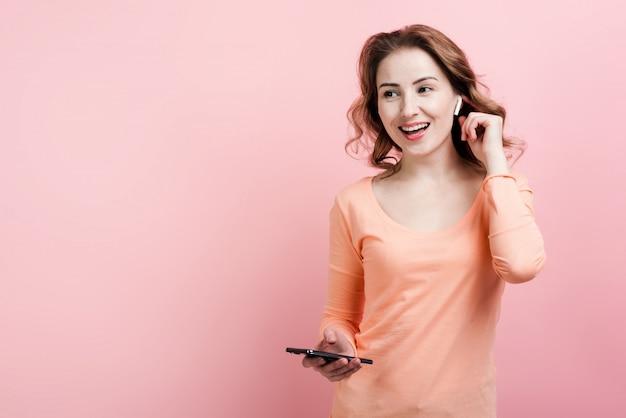 Vrolijke vrouw in airpods met telefoon het dansen