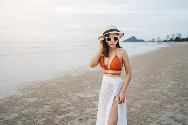 Vrolijke vrouw in bikini die zich bij het overzeese strand bevindt