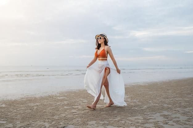 Vrolijke vrouw in bikini wandelen op het strand