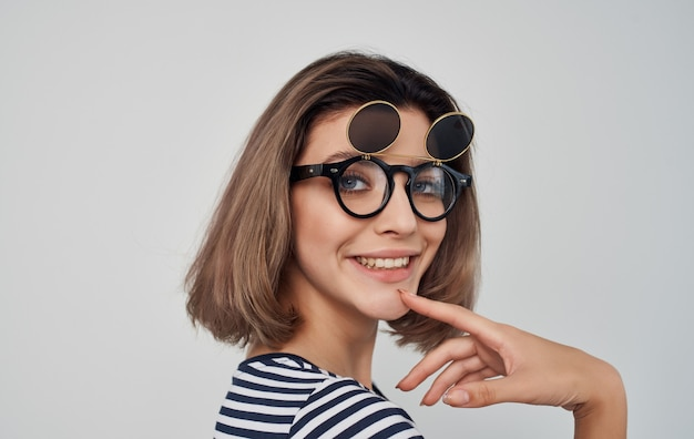 Vrolijke vrouw in de gestreepte glimlach van de t-shirt dubbele bril
