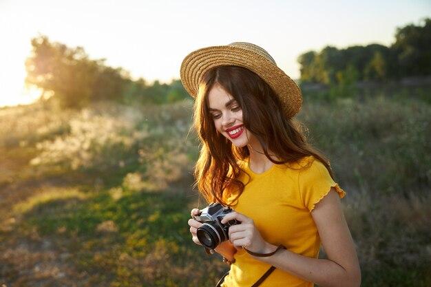 Vrolijke vrouw in de natuur met een camera