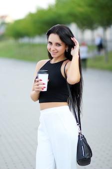 Vrolijke vrouw in de straat het drinken ochtendkoffie in zonneschijn