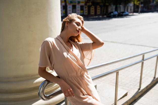 Vrolijke vrouw in de straat in zonneschijn licht, aantrekkelijk blondemeisje bij de zomerdag