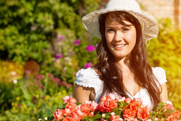 Vrolijke vrouw in de zomer bloementuin