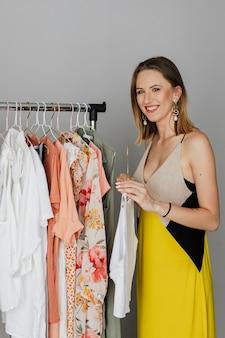Vrolijke vrouw in een gele jurk die een doek uit een rek selecteert