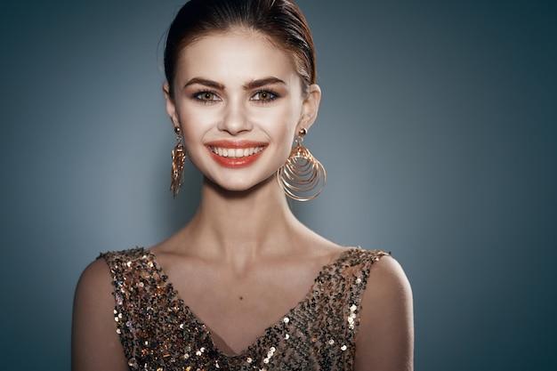 Vrolijke vrouw in een gouden jurk sieraden oorbellen mode glamour
