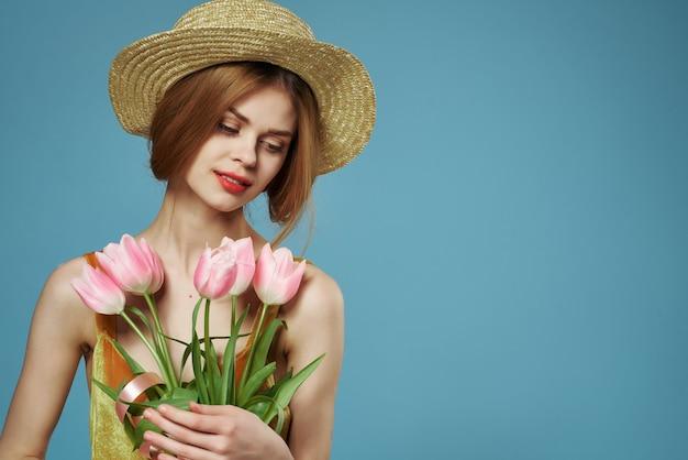 Vrolijke vrouw in een hoed boeket bloemen mimosa lente blauwe achtergrond
