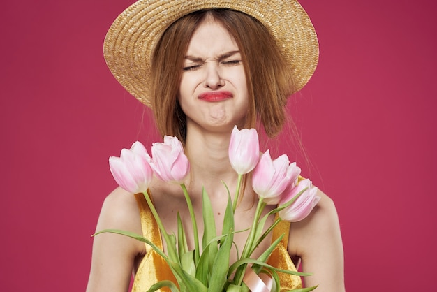 Vrolijke vrouw in een hoedenjurk en een boeket van bloemen roze close-up als achtergrond