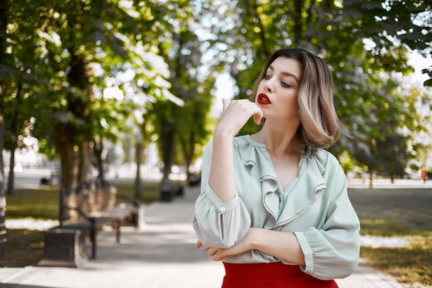 Vrolijke vrouw in een rode rok op het plein in de stadswandeling