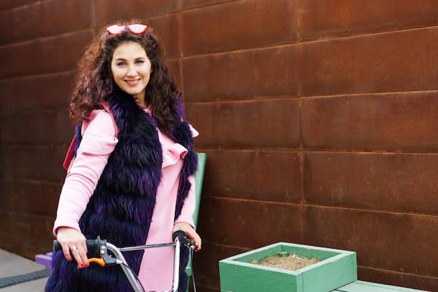 Vrolijke vrouw in een roze kleding en een paarse bontkaap die een autoped berijdt op het stedelijke landschap.