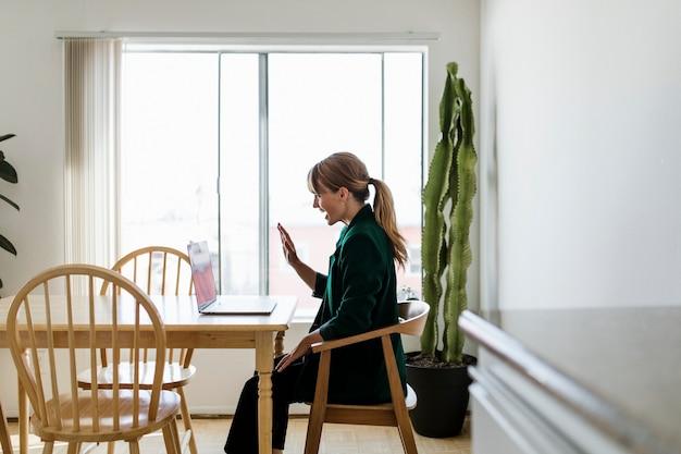 Vrolijke vrouw in een videogesprek terwijl ze thuis werkt tijdens een pandemie van het coronavirus