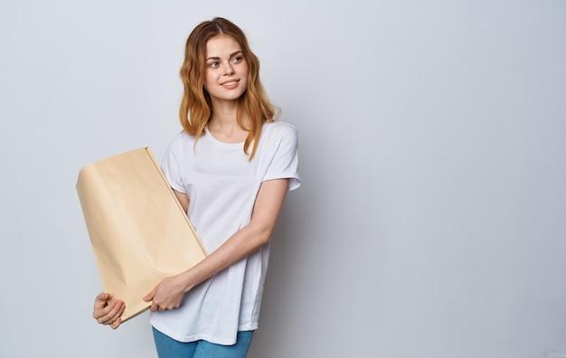 Vrolijke vrouw in een wit t-shirt met een pakket in haar handen winkelen