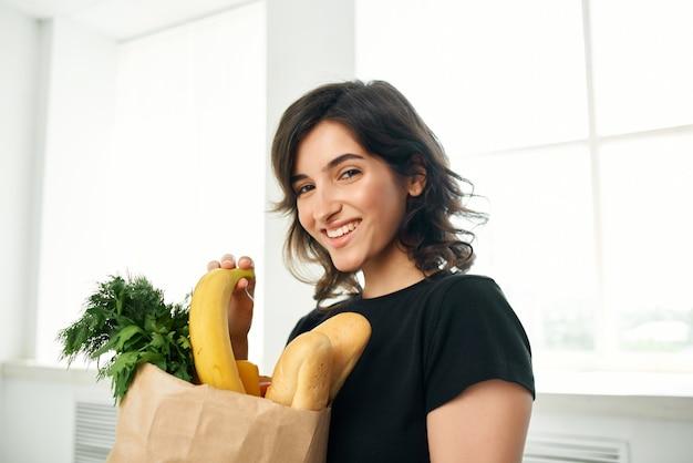 Vrolijke vrouw in een zwart t-shirtpakket met gezonde voedingsproducten