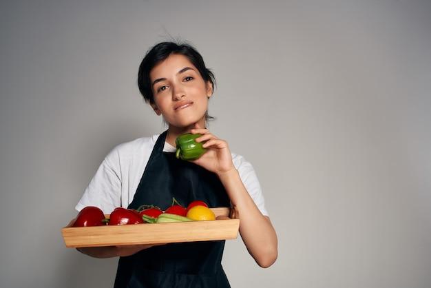 Vrolijke vrouw in een zwarte schort groenten huishoudelijk werk koken